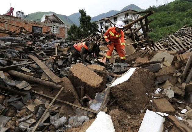 a-rescuer-uses-a-sniffer-dog-to-search-for-survivors-tuesday-at-a-collapsed-house-after-sundays-61-magnitude-earthquake-in-the-town-of-longtoushan-in-ludian-county-in-southwest-chinas-yunnan-province