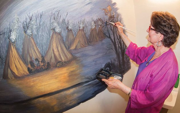 fairfield-bay-artist-doris-sexson-works-on-a-mural-in-the-restroom-of-the-log-cabin-museum-at-the-indian-hills-country-club-in-fairfield-bay-the-mural-depicts-native-americans-and-their-tepees