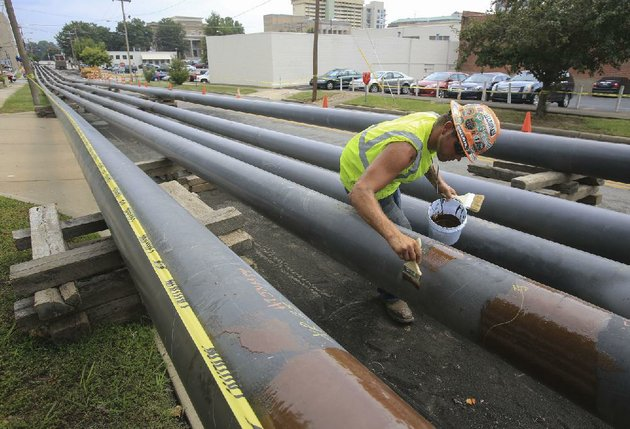 kyle-jimeson-with-michels-corporation-of-wisconsin-coats-pipes-with-a-sealant-thursday-while-working-on-a-new-gas-pipeline-that-will-replace-the-gas-pipelines-on-the-broadway-bridge