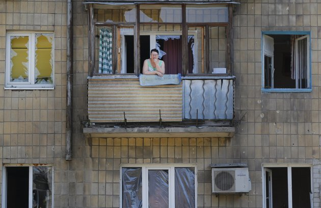 a-local-woman-stands-on-her-damaged-balcony-after-morning-shelling-in-donetsk-eastern-ukraine-saturday-aug-9-2014-several-shells-fell-this-morning-in-a-northern-donetsk-neighborhood-near-the-airport-no-human-casualties-were-registered