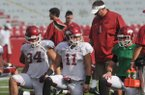 Arkansas coach Bret Bielema talks with his players Hunter Henry, AJ Derby and Brandon Allen as they warm up for practice Saturday, Aug. 9, 2014, at Razorback Stadium in Fayetteville.