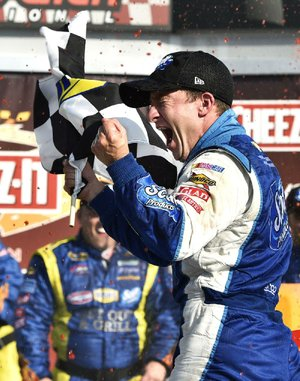 AJ Allmendinger waves the checkered flag as he celebrates in Victory Lane after winning a NASCAR Sprint Cup Series auto race at Watkins Glen International, Sunday, Aug. 10, 2014, in Watkins Glen, N.Y. (AP Photo/Derik Hamilton)