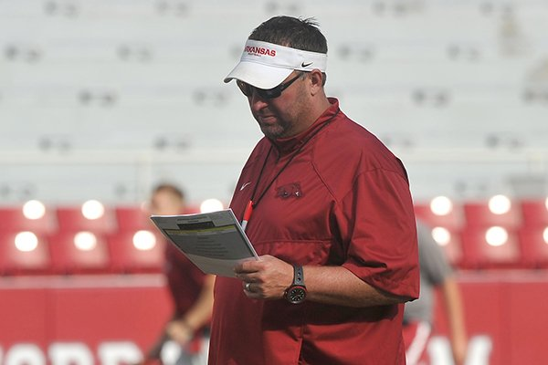 Arkansas coach Bret Bielema reads his notes during a practice Saturday, Aug. 9, 2014 at Razorback Stadium in Fayetteville.