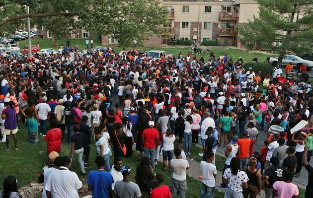 a-large-crowd-gathers-at-the-candlelight-vigil-sunday-evening-aug-10-2014-in-ferguson-mo-a-few-thousand-people-crammed-the-street-where-a-black-man-was-shot-multiple-times-by-a-suburban-st-louis-police-officer-the-candlelight-vigil-sunday-night-was-for-18-year-old-michael-brown-who-died-a-day-earlier-police-say-he-was-unarmed