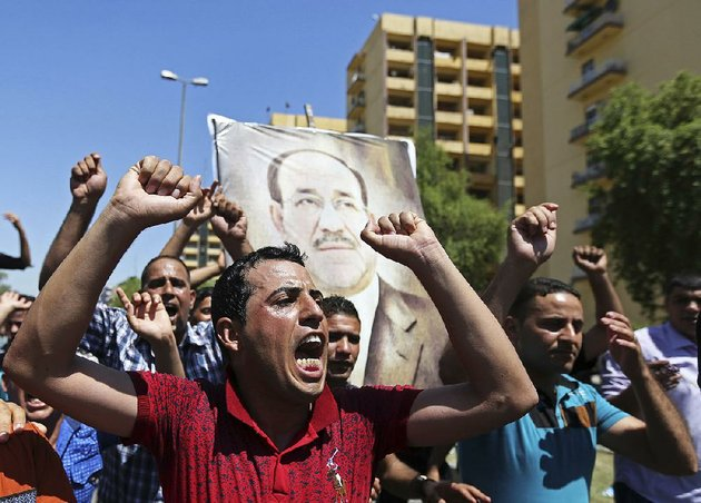 iraqis-chant-pro-government-slogans-and-display-placards-bearing-a-picture-of-embattled-prime-minister-nouri-al-maliki-during-a-demonstration-in-baghdad-iraq-monday-aug-11-2014-al-maliki-is-taking-his-struggle-to-keep-his-job-to-the-courts-after-announcing-he-will-file-a-legal-complaint-on-monday-against-the-countrys-newly-elected-president-president-barack-obama-warned-americans-on-saturday-that-the-new-campaign-to-bring-security-in-iraq-requires-military-and-political-changes-and-is-going-to-be-a-long-term-project-ap-photo-hadi-mizban