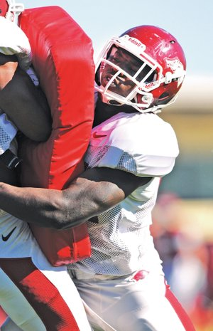 FILE PHOTO SAMANTHA BAKER • @NWASAMANTHA Otha Peters uses as much force as he can to knock his teammate out of the way April 22 during spring football practice at University of Arkansas in Fayetteville.