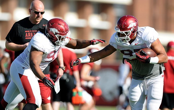 Rory Segrest, back, watches on as Darius Philon, left, tries to tackle Tevin Beanum, right, at spring football practice Tuesday, April 22, 2014, at University of Arkansas in Fayetteville.