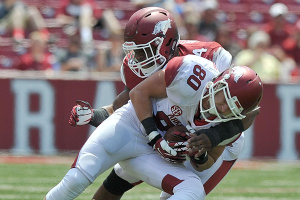 Arkansas receiver Drew Morgan (80) is tackled by linebacker Braylon Mitchell during the Red-White Game on Saturday, April 26, 2014 at Razorback Stadium in Fayetteville.