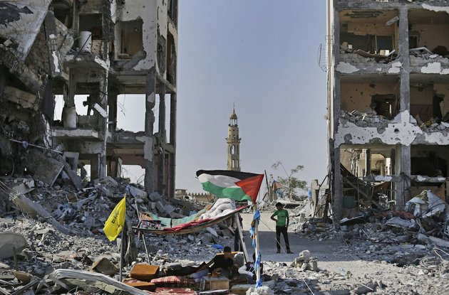 back-dropped-by-the-damaged-minaret-of-the-al-azba-mosque-palestinians-sit-under-a-tent-they-erected-by-the-rubble-of-houses-destroyed-by-israeli-strikes-during-the-war-in-the-town-of-beit-lahiya-northern-gaza-strip-on-tuesday-aug-12-2014