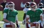 Arkansas quarterbacks Austin Allen (left) and Rafe Peavey stretch prior to an April 20, 2014 practice in Fayetteville.