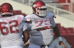 Arkansas offensive lineman Sebastian Tretola goes through drills Saturday, Aug. 9, 2014 at Razorback Stadium in Fayetteville.