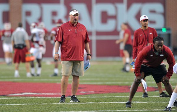 Arkansas head football coach Bret Bielema works with his team during practice Wednesday, Aug. 13, 2014, at Razorback Stadium in Fayetteville.