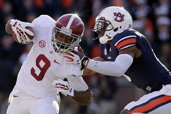 In the Nov. 30, 2013, file photo, Auburn linebacker Jake Holland (5) pushes Alabama wide receiver Amari Cooper (9) out-of-bounds during the first half of an NCAA college football game in Auburn, Ala. Alabama is hoping for another powerful rebound to once again go from a big beating in the Big Easy, to national dominance. (AP Photo/Dave Martin, File)