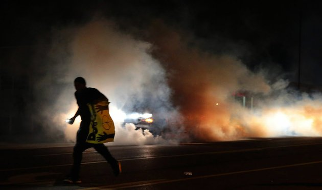 a-protestor-runs-down-the-street-to-escape-tear-gas-fired-at-demonstrators-on-sunday-aug-17-2014-in-ferguson-mo-as-night-fell-sunday-in-ferguson-another-peaceful-protest-quickly-deteriorated-after-marchers-pushed-toward-one-end-of-a-street-police-attempted-to-push-them-back-by-firing-tear-gas-and-shouting-over-a-bullhorn-that-the-protest-was-no-longer-peaceful