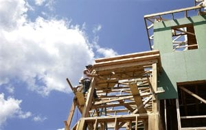 A worker clings to the frame of a house being built in Belmar, N.J., on July 30. Home construction increased 15.7 percent in July, the Commerce Department reported Tuesday.