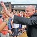 STAFF PHOTO BEN GOFF • @NWABenGoff Poore high-fives students after getting doused in ice water...
