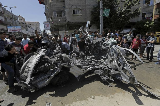 palestinians-move-the-wreckage-of-a-vehicle-following-an-israeli-airstrike-off-the-main-street-in-gaza-city-in-the-northern-gaza-strip-on-thursday-aug-21-2014-at-least-two-were-killed-in-the-car-outside-a-grocery-shop-and-a-few-others-were-wounded-by-an-israel-airstrike-on-a-gaza-city-street-according-to-the-palestine-red-crescent-society