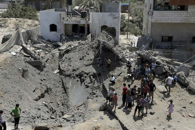 palestinians-look-at-a-crater-made-after-a-house-was-hit-by-an-israeli-airstrike-in-gaza-in-the-northern-gaza-strip-on-friday-aug-22-2014