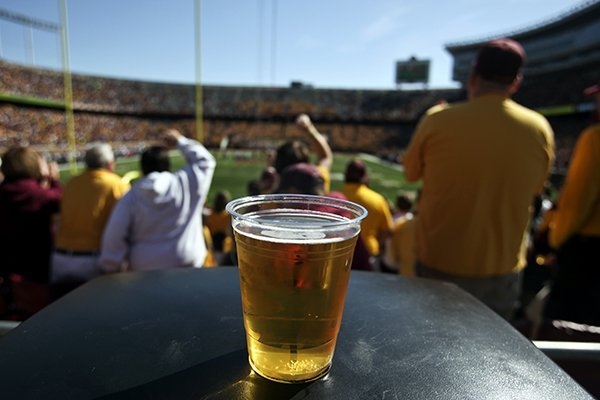 In this Sept. 8, 2012, photo, a beer sits atop a garbage can as Minnesota college football fans fans cheer a first quarter play against New Hampshire at TCF Bank Stadium in Minneapolis, Minn. A growing number of schools are capitalizing on fans' taste for the suds by bringing the party inside, opening taps in concourses that traditionally have been alcohol-free zones.(AP Photo/The Star Tribune, David Joles)