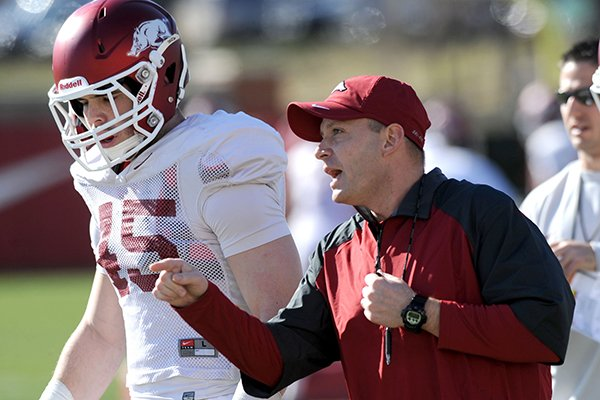 Arkansas defensive coordinator Robb Smith directs his players as linebacker Alex Brignoni (45) listens during practice Thursday, March 20, 2014, at the UA practice field in Fayetteville.