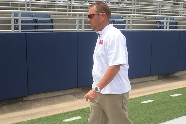 Mississippi coach Hugh Freeze walks to join the NCAA college football team for a photo during media day in Oxford, Miss., on Friday, Aug. 1, 2014. (AP Photo/Oxford Eagle, Bruce Newman)