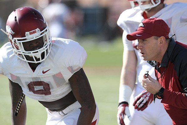 Arkansas defensive coordinator Robb Smith directs cornerback Will Hines (9) during practice Thursday, March 20, 2014, at the UA practice field in Fayetteville.