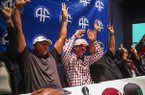 North Little Rock receiver K.J. Hill, center, plaid, , calls the Hogs with his step-father Montez Peterson, left, father Keith Hill, right, and other family members after announcing Friday his oral commitment to Arkansas during a news conference at the Arkansas Sports Hall of Fame in North Little Rock.