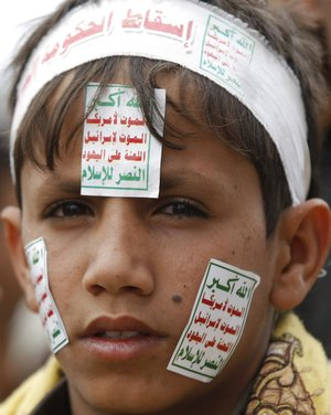 "A Yemeni boy wearing a headband with Arabic writing reads,""Down with the government of corruption."" and posters on his face reads,""Allah is the greatest. Death to America. Death to Israel. A curse on the Jews. Victory to Islam."" attends a demonstration demanding the government to step down in Sanaa, Yemen, Friday, Aug. 29, 2014. Hundreds of thousands of Yemenis rallied in the capital and across the country against an armed Shiite rebel group which has been holding its own sit-in demanding a new government and the reinstatement of fuel subsidies."