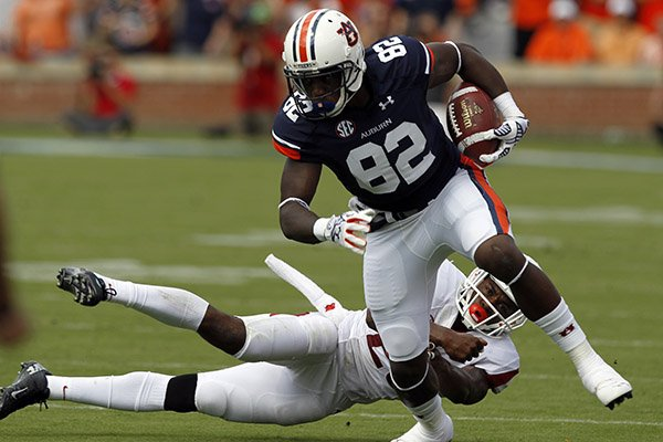 Auburn wide receiver Melvin Ray (82) catches a pass and breaks away from Arkansas safety Rohan Gaines (26) for a touchdown during the first half of an NCAA college football game on Saturday, Aug. 30, 2014, in Auburn, Ala. (AP Photo/Butch Dill)