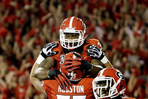 Georgia's Todd Gurley, top, is hoisted into the air by teammate Kolton Houston after scoring a touchdown in the second half of an NCAA college football game against Clemson, Saturday, Aug. 30, 2014, in Athens, Ga. Georgia won 45-21. (AP Photo/David Goldman)