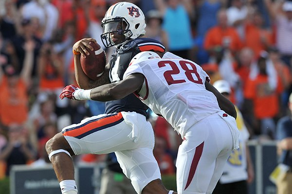 Auburn quarterback Nick Marshall pushes past Arkansas defender Josh Liddell to score a touchdown in the third quarter of a game Saturday, Aug. 30, 2014 at Jordan-Hare Stadium in Auburn, Ala.