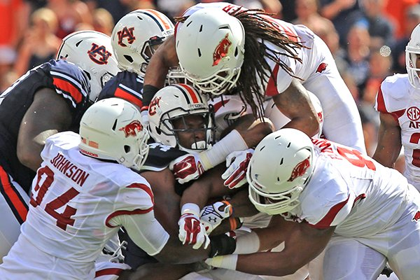 Arkansas defenders swarm Auburn running back Cameron Artis-Payne on Saturday, Aug. 30, 2014 at Jordan-Hare Stadium in Auburn, Ala.