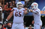 Arkansas center Mitch Smothers (65) and quarterback Brandon Allen point out instructions prior to a play Saturday, Aug. 30, 2014 at Jordan-Hare Stadium in Auburn, Ala.