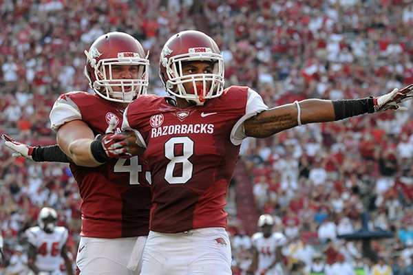 Austin Jones, left, hugs Tevin Mitchel Saturday, Aug. 31, 2013 after a tackle during the third quarter of the game against Louisiana-Lafayette at Razorback Stadium in Fayetteville.