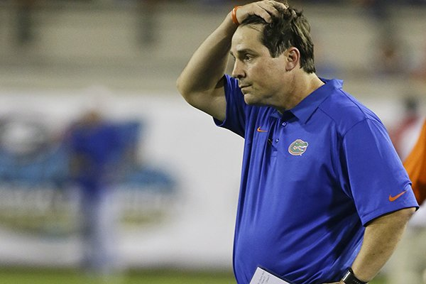 In this Nov. 2, 2013, file photo, Florida head coach Will Muschamp holds his hand on his head as he watches the final moments of an NCAA college football game against Georgia in Jacksonville, Fla. Muschamp came to his own defense Wednesday, Sept. 3, 2014, ripping critics who questioned his decision to reinstate three players suspended for a season opener that lasted just 10 seconds. (AP Photo/John Raoux, File)