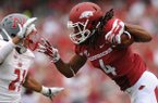 Arkansas receiver Keon Hatcher (4) reaches to fend off Nicholls defensive back Josh Singleton during the second quarter Saturday, Sept. 6, 2014, at Razorback Stadium in Fayetteville