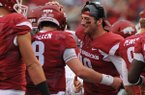 Arkansas quarterback Brandon Allen, center, greets his brother and backup Austin Allen (8) after an Arkansas touchdown against Nicholls during the fourth quarter Saturday, Sept. 6, 2014, at Razorback Stadium in Fayetteville.