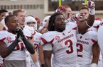 Arkansas running back Alex Collins (3) and other players celebrate after defeating Texas Tech in Jones AT&T Stadium in Lubbock, Texas on Saturday Sept. 13, 2014.