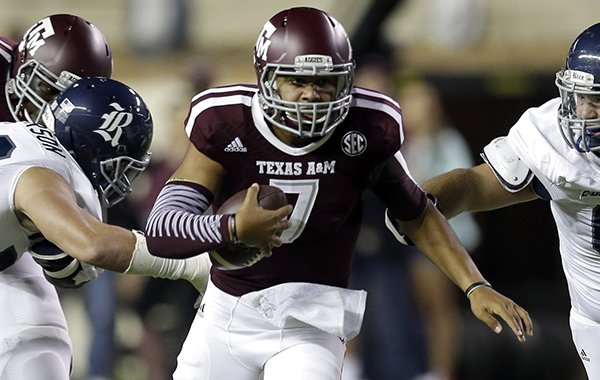 Texas A&M quarterback Kenny Hill (7) rushes for a gain as Rice defensive end Grant Peterson, left, and Brad Luvender (69) defend during the first quarter of an NCAA college football game Saturday, Sept. 13, 2014, in College Station, Texas. (AP Photo/David J. Phillip)
