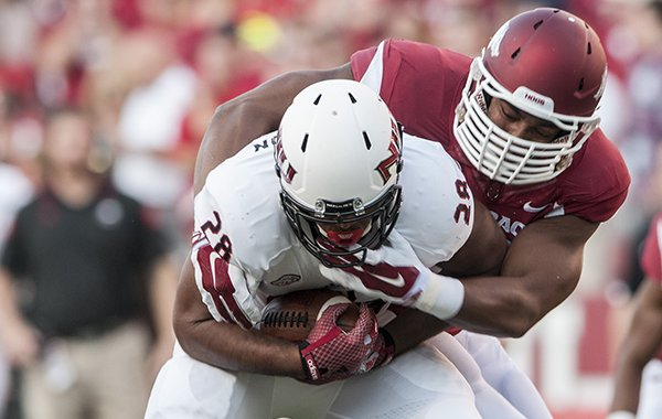 Arkansas defensive end Trey Flowers tackles Northern Illinois University tailback Joel Bouagnon in the first quarter Saturday, Sept. 20, 2014 at Razorback Stadium in Fayetteville.