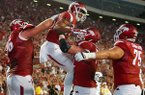 Arkansas offensive tackle Frank Ragnow, right, lifts wide receiver Jared Cornelius as they celebrate Cornelius' touchdown against Northern Illinois in the second quarter of an NCAA college football game in Fayetteville.  Saturday, Sept. 20, 2014.