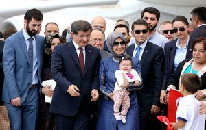 Turkish Prime Minister Ahmet Davutoglu, center left, stands with freed hostages at the airport in Ankara, Turkey, Saturday, Sept. 20, 2014. Dozens of Turkish hostages seized by Islamic militants in Iraq three months ago were freed and safely returned to Turkey on Saturday ending Turkey's most serious hostage crisis. The 49 hostages were captured from the Turkish Consulate in Mosul, Iraq on June 11, when the Islamic State group overran the city in its surge to seize large swaths of Iraq and Syria. (AP Photo)