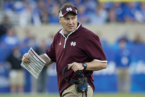 Mississippi State head coach Dan Mullen checks on the condition of an injured player during the second half of an NCAA college football game against Kentucky at Commonwealth Stadium in Lexington, Ky., Saturday, Oct. 25, 2014. Mississippi State beat Kentucky 45-31. (AP Photo/David Stephenson)