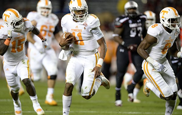 Tennessee quarterback Joshua Dobbs (11) takes off on a fourth-down play, with seconds left on the clock, to score a 36-yard touchdown during the first half of an NCAA college football game against South Carolina in Columbia, S.C., Saturday, Nov. 1, 2014. (AP Photo/ Richard Shiro)