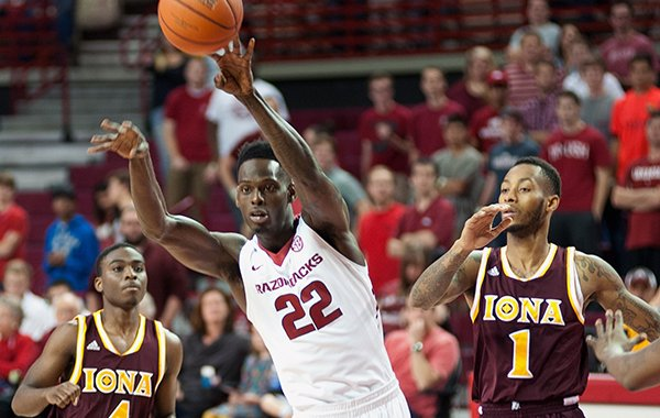Arkansas' Jacorey Williams (22) passes the ball next to Iona's Schadrac Casimir (4) and Isaiah Williams (1) in the first half of an NCAA college basketball game in Fayetteville, Ark., Sunday, Nov. 30, 2014. (AP Photo/Sarah Bentham)