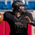 Bentonville junior quarterback Kasey Ford drops back to pass while being pressured by Fayetteville s...