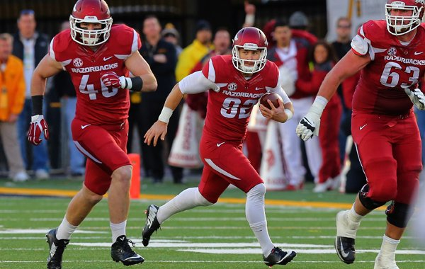 Arkansas punter Sam Irwin-Hill, center, rolls out for yardage Friday, Nov. 28, 2014, after faking a punt in the third quarter against Missouri in Columbia, Mo.