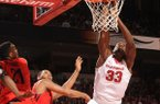 Arkansas' Moses Kingsley (33) attempts to dunk the ball as he is hit by Dayton's Dyshawn Pierre, left, during the second half Saturday, Dec. 13, 2014, at Bud Walton Arena in Fayetteville.