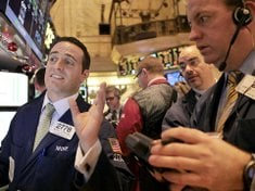 Traders watch stocks ...