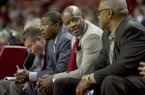 Arkansas head coach Mike Anderson, second from right, talks to his assistant coaches from his bench during the second half of an NCAA college basketball game against Utah Valley on Saturday, Jan. 3, 2015, in Fayetteville, Ark. Arkansas defeated Utah Valley 79-46. (AP Photo/Gareth Patterson)